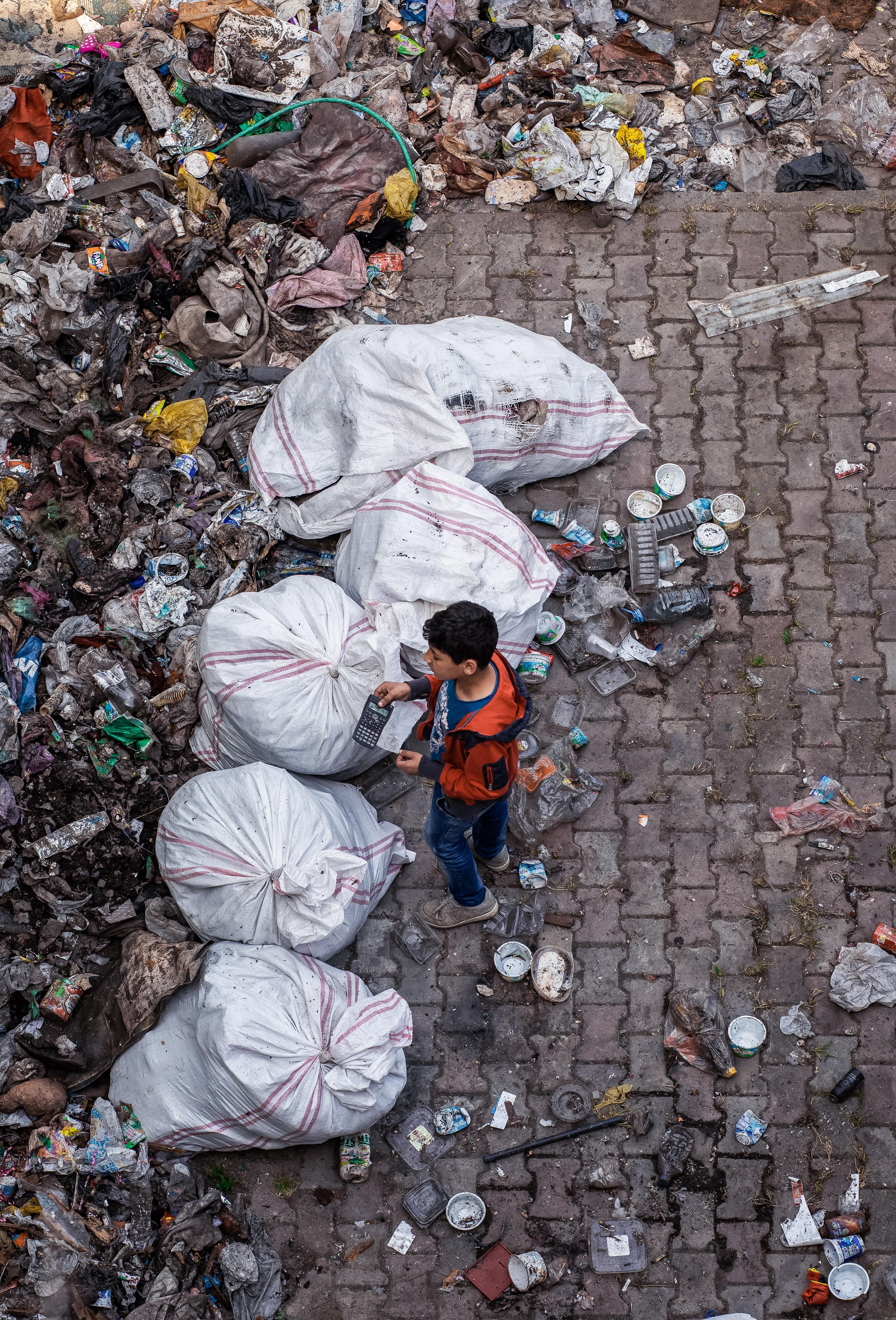 Ein Junge vor einem riesigen Müllberg.
